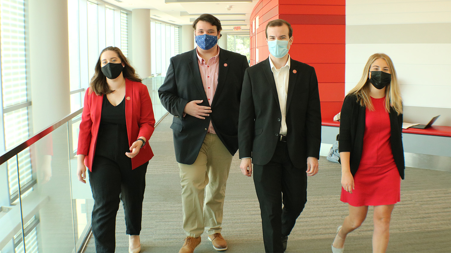 Four Student Government leaders walk side by side through a hallway in Talley Student Union