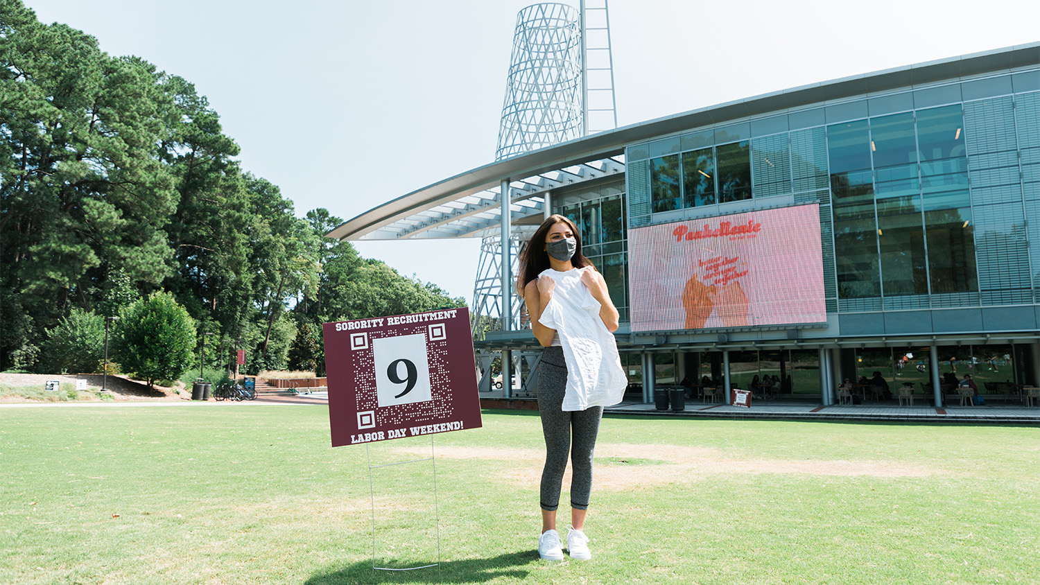 A new member of a Panhellenic organization holds up her T-shirt in front of Talley Student Union