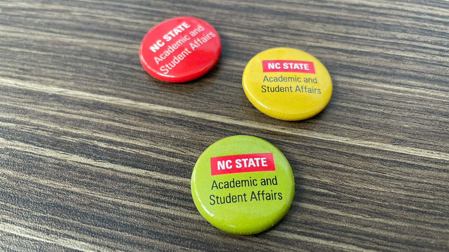 Red, yellow and green buttons with the NC State Academic and Student Affairs logo on them