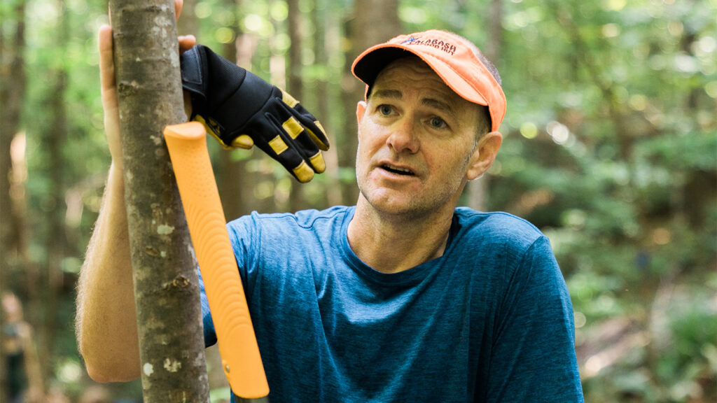 Tommy Holden leans against a small tree in Lake Raleigh Woods while working on a bike trail reroute project.