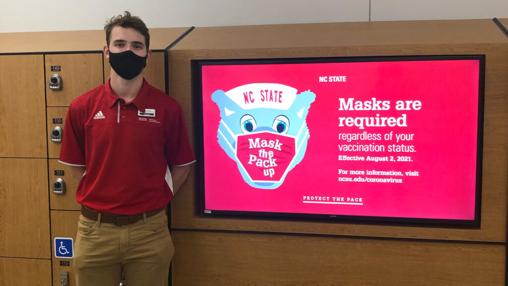 """Owen Hanna, stands next to lockers wearing a black face covering and a red polo shirt, standing next to a sign that says """"Masks are required regardless of your vaccination status."""""""