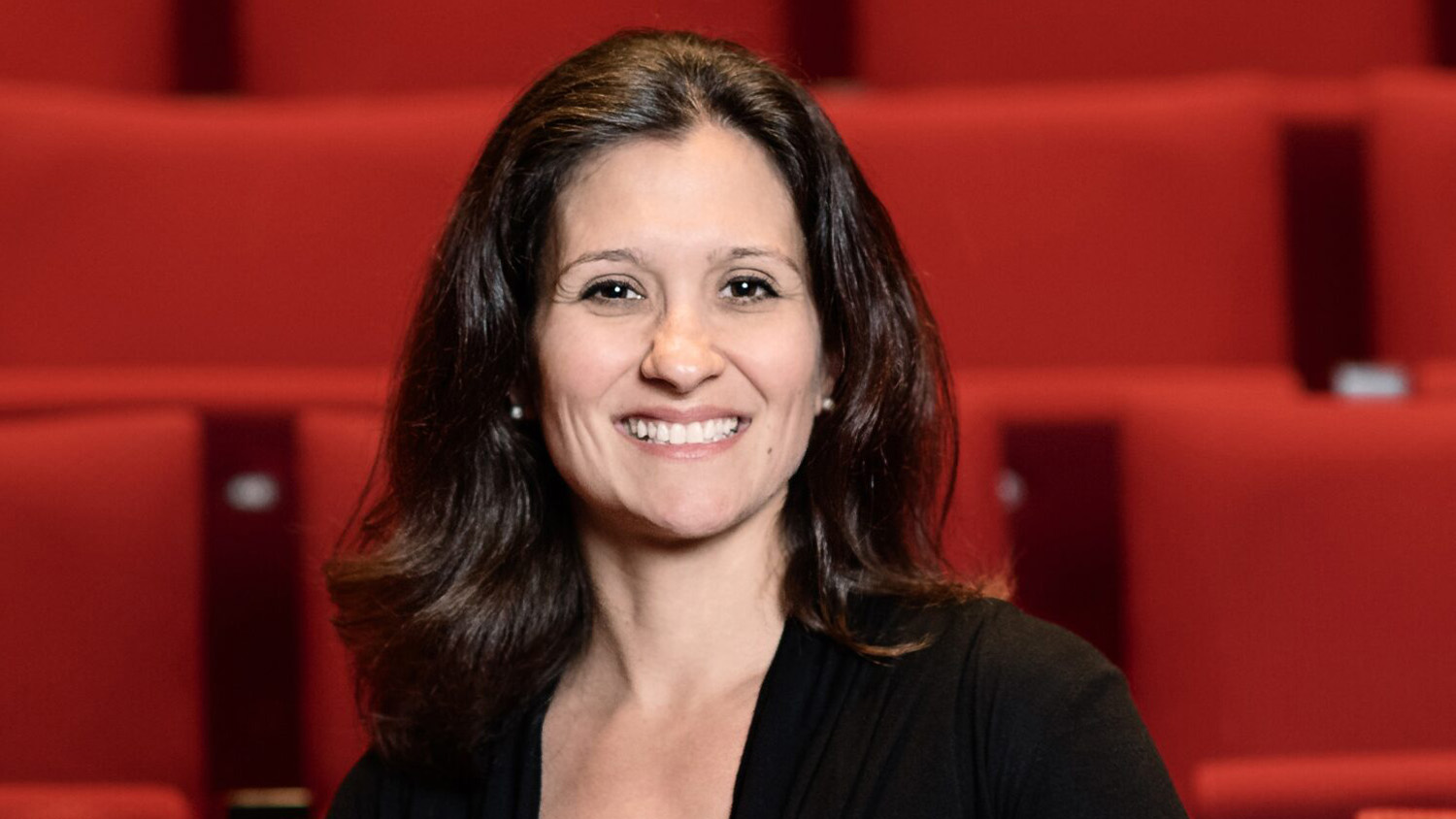 Tara Mullins in front of red seats in Thompson Theatre