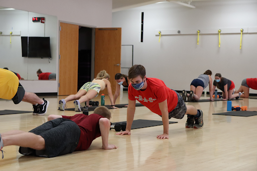 Students do pushups on a wood floor