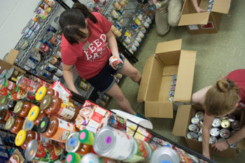 Volunteers move food to the new Feed the Pack Food Pantry