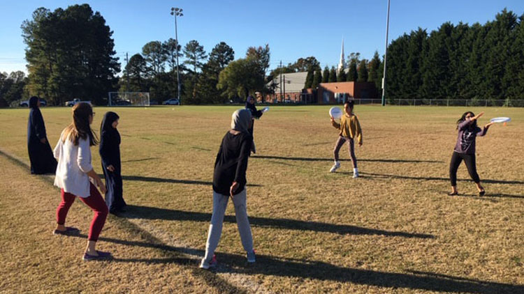 NC State students teaching ultimate frisbee