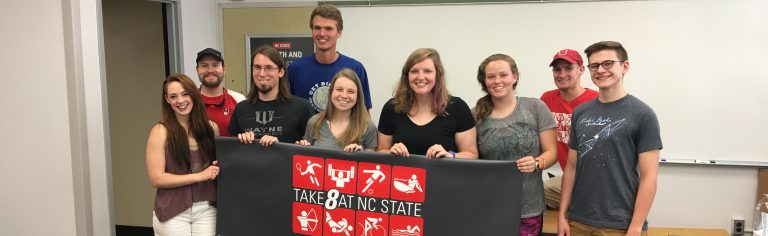 Students holding a Take 8 at State banner