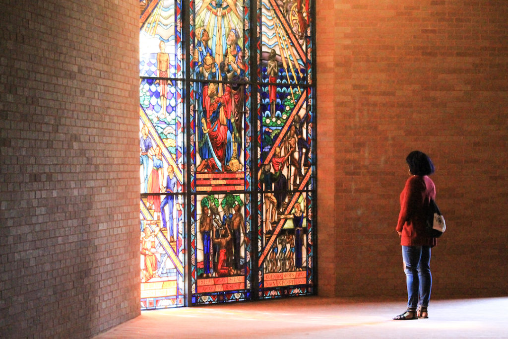 Student stands in front of a stained glass window