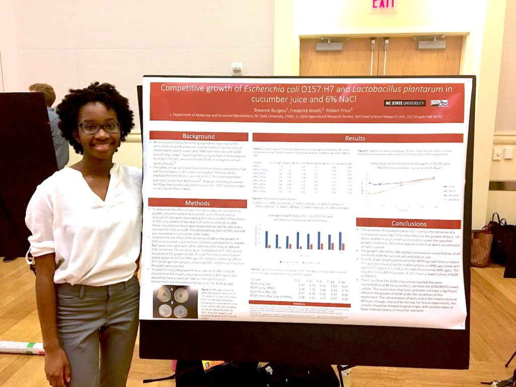 Burgess stand by her bacterial studies presentation poster.