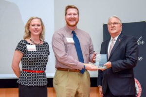 Brian Mathis receives Award of Excellence from Chancellor Randy Woodson and Senior Associate Vice Chancellor in the Division of Academic and Student Affairs Lisa Zapata