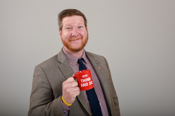 Brian Mathis holds a coffee cup and smiles at the camera.