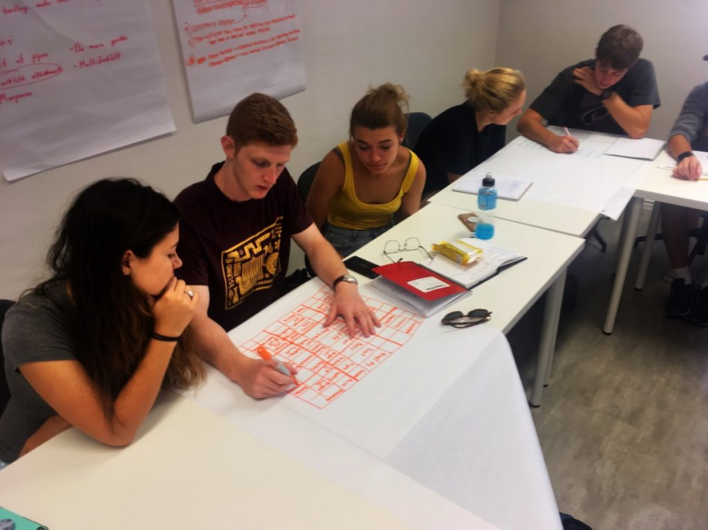 Students sit at a table working on a project.
