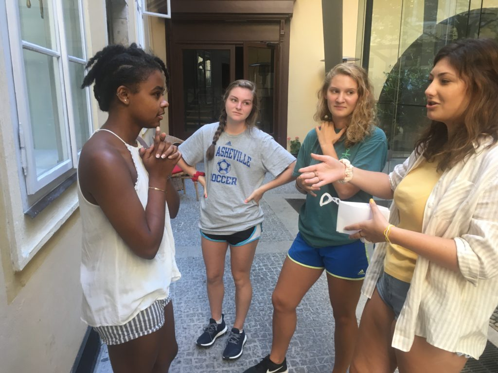 Students stand together in Prague, discussing a topic.
