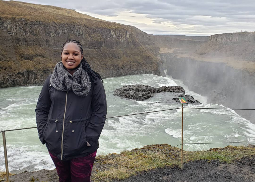 Safari Richardson stands near a waterfall in Iceland