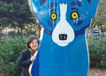 Holly Hurlburt stands next to an art installation featuring a cartoon dog