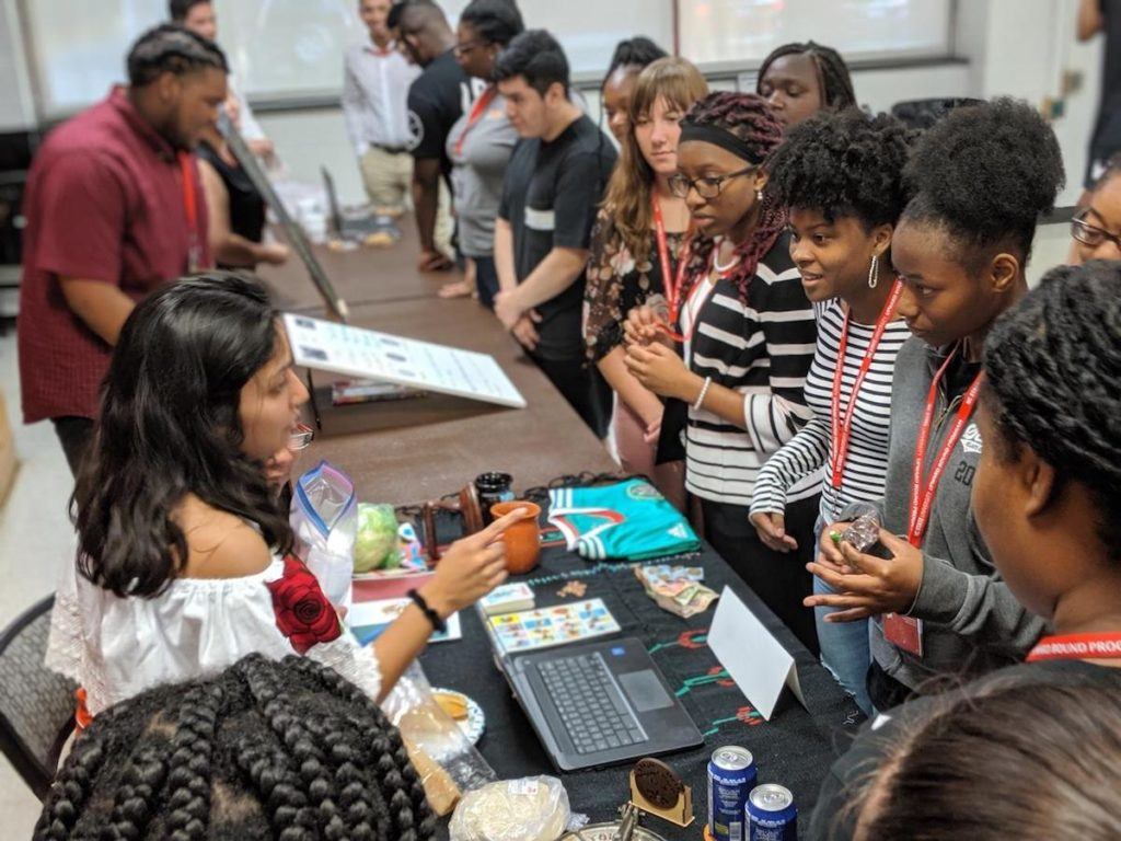 Students with TRIO Upward Bound stand around a table asking questions to presenters