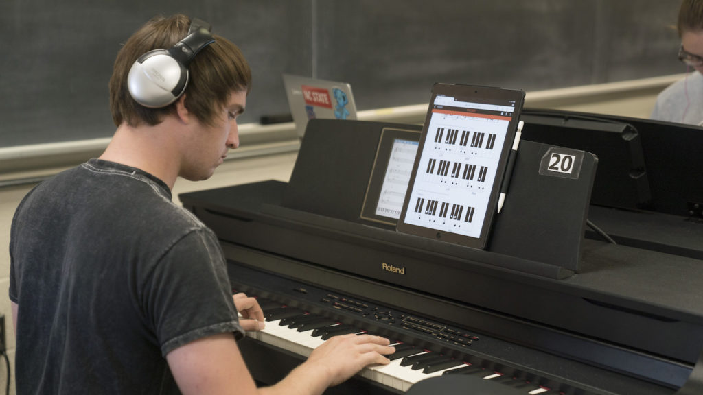 Lucas Sanders practices playing piano using the Piano+ interactive method book created through a DELTA Grant in partnership with Olga Kleiankina from the Department of Music. Photo by Erin Zanders. The student is playing piano and has a tablet in front of him with the Piano+ loaded on the screen.
