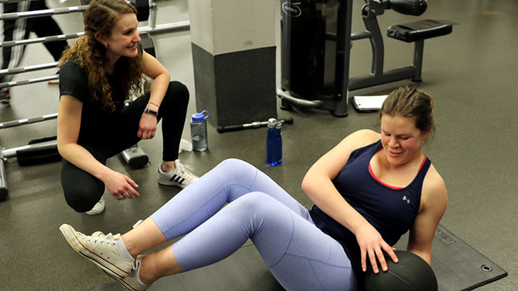 Whitney Knollenberg working with a student personal trainer.