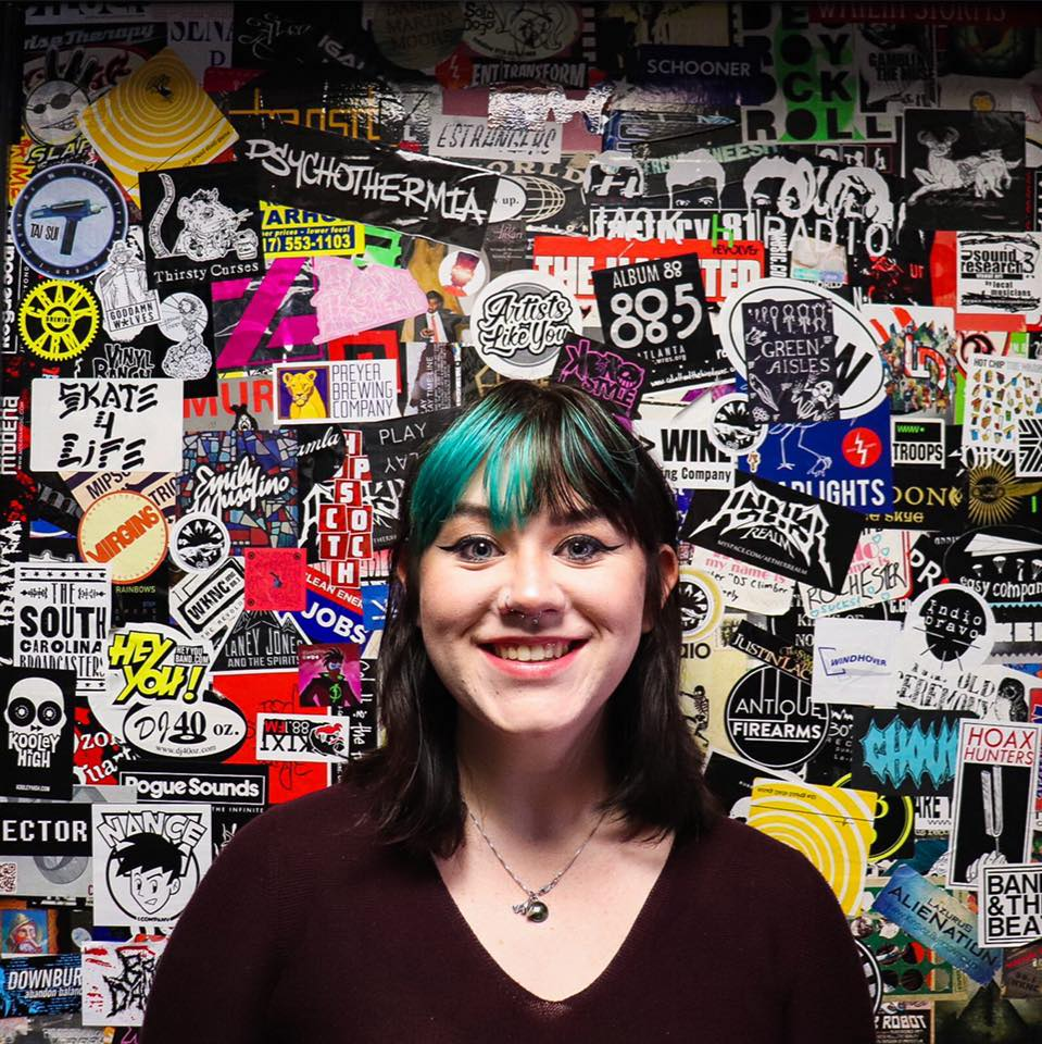 Person with green hair standing in front of a heavily stickered door