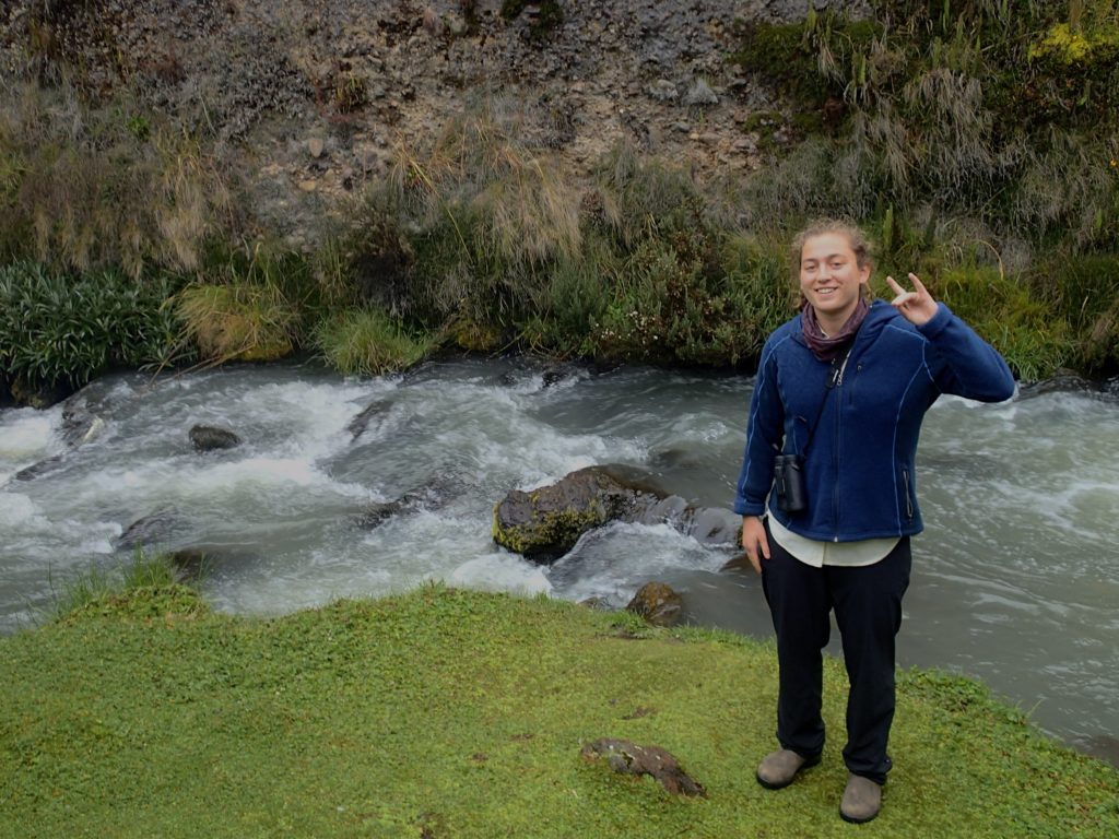 Anna Poston makes a Wolfie sign by a stream
