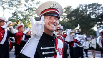 Thomas Peters smiles and does the wolfie in his band uniform