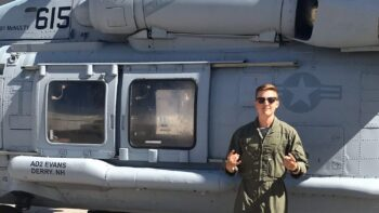 Garrett Welsh in front of a Navy helicopter