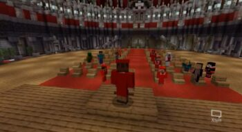 Tanner Compton's Minecraft character, dressed in red graduation robes, addresses an audience of other Minecraft players/NC State graduates in the Minecraft version of PNC Arena
