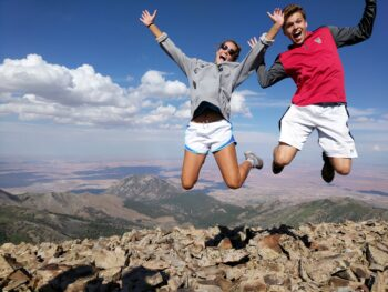 A male and female student jump for a photo opp in front of a canyon