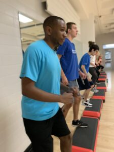 Students participate in a high-stepping workout during a Health and Exercise Studies course