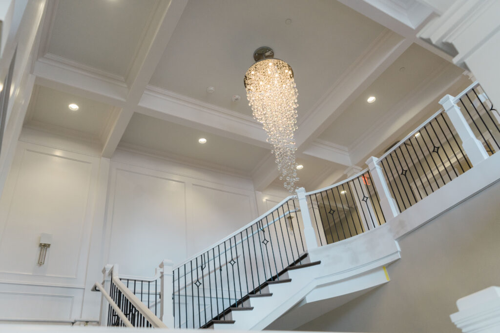 An elegant chandelier hangs over a stairwell in one of the houses